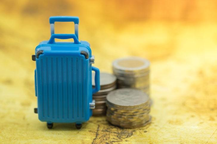 Blue miniature baggage with stack of coins on world map
