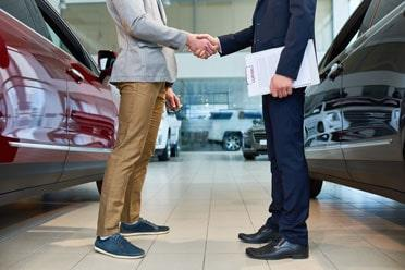 Customer and seller shaking hands at car hire dealership