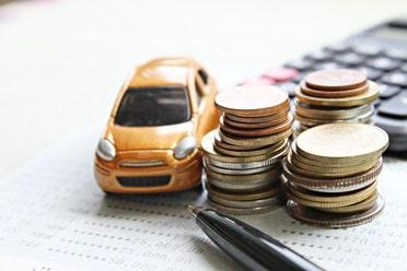 Miniature car model, coins stacked on desk