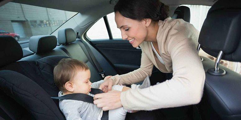 Woman putting seatbelt on child