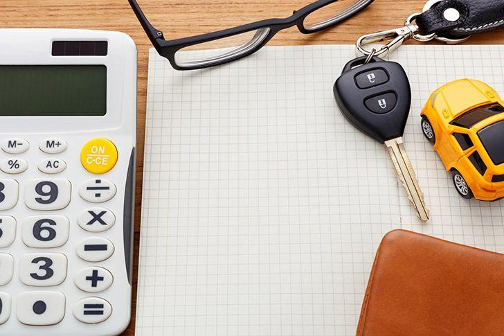 Notebook with car key and calculator