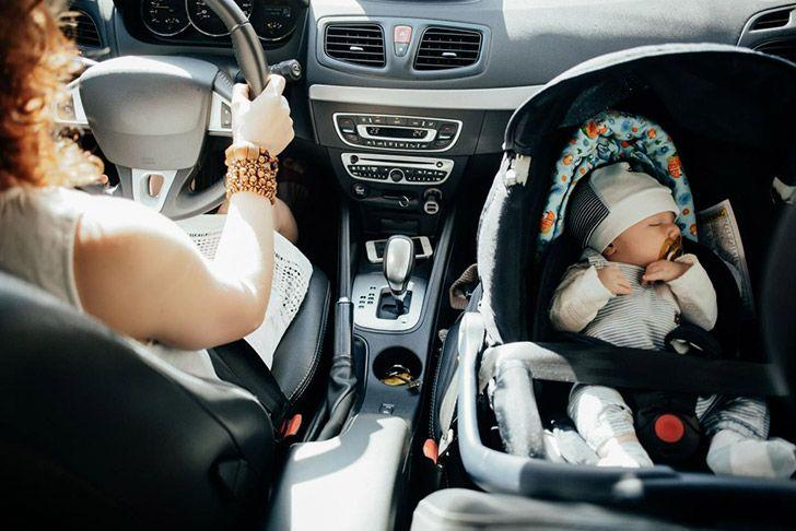 Mother driving with baby in car-seat