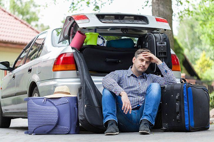 Stressed out man loading holiday suitcases into the car