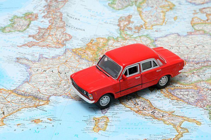 Toy car driving over map of Europe