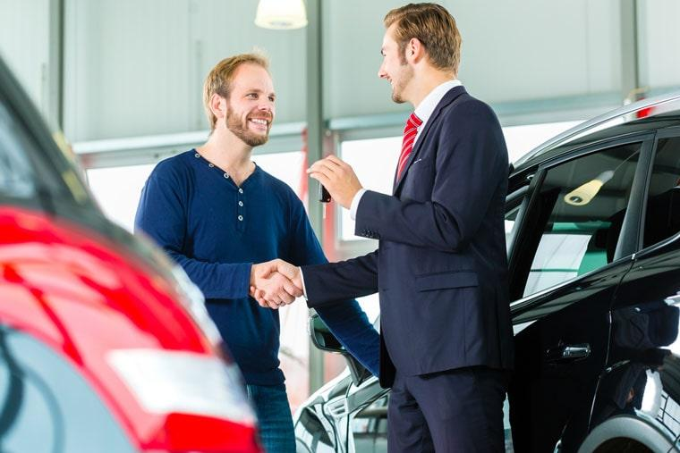Young man and seller with auto in car hire dealership