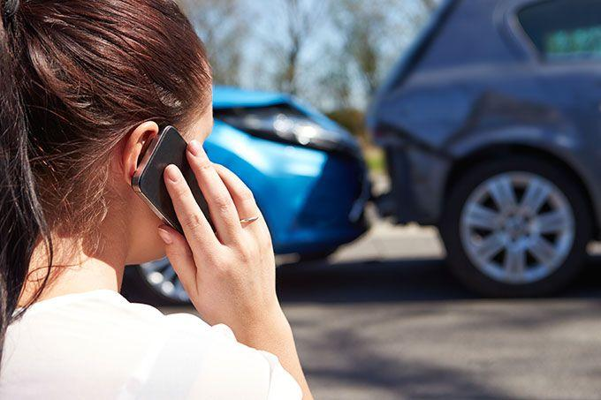 Woman calling insurance company after car accident