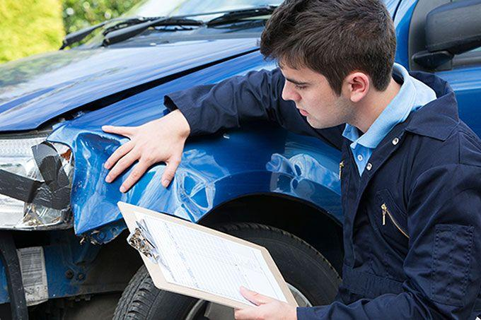 Man inspecting damage on a written-off car